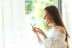 Muchacha que usa un teléfono cerca de una ventana Fotos de archivo