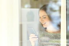 Muchacha que usa un teléfono elegante al lado de una ventana Foto de archivo