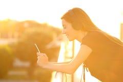 Muchacha que usa un teléfono elegante en un balcón en la puesta del sol Foto de archivo