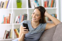 Muchacha que usa un teléfono elegante en un sofá en casa Imagenes de archivo