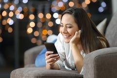 Muchacha que usa un teléfono elegante que miente en un sofá en casa Imagen de archivo libre de regalías