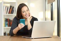 Muchacha que usa un teléfono y un ordenador portátil elegantes en una tabla en casa Foto de archivo libre de regalías