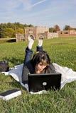 Muchacha que usa una computadora portátil Fotos de archivo