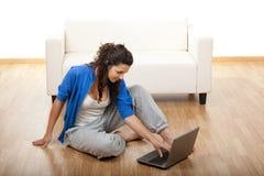 Muchacha que usa una computadora portátil Fotografía de archivo libre de regalías