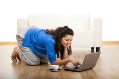 Muchacha que usa una computadora portátil Imagenes de archivo