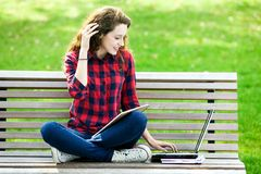Muchacha que usa una computadora portátil en un banco Fotos de archivo libres de regalías