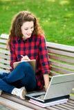 Muchacha que usa una computadora portátil en un banco Imagen de archivo libre de regalías
