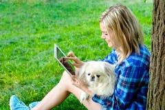 Muchacha que usa una tableta digital al aire libre Imagen de archivo