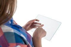 Muchacha que usa una tableta digital de cristal contra el fondo blanco Imágenes de archivo libres de regalías