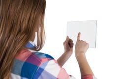 Muchacha que usa una tableta digital de cristal contra el fondo blanco Fotografía de archivo libre de regalías