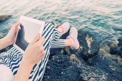 Muchacha que usa una tableta digital por el mar Foto de archivo