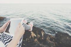 Muchacha que usa una tableta digital por el mar Foto de archivo libre de regalías