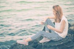 Muchacha que usa una tableta digital por el mar Fotografía de archivo libre de regalías