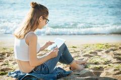 Muchacha que usa una tableta digital por el mar Fotos de archivo