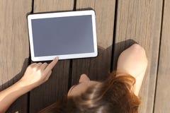 Muchacha que usa y mostrando una pantalla en blanco de la tableta Imágenes de archivo libres de regalías