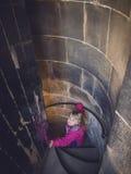 Muchacha que va abajo de las escaleras espirales Foto de archivo