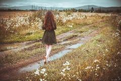 Muchacha que va en el camino rural Fotos de archivo