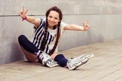 Muchacha que va rollerblading poner que se sienta en patines en línea Fotografía de archivo libre de regalías
