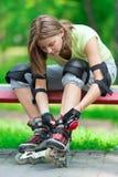 Muchacha que va rollerblading sentarse en el banco que pone en skat en línea Fotografía de archivo libre de regalías