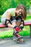 Muchacha que va rollerblading sentarse en el banco que pone en skat en línea Foto de archivo libre de regalías