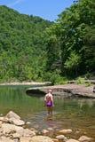Muchacha que vadea en corriente de la montaña Fotos de archivo