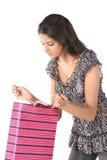 muchacha que ve el bolso de compras con sorpresa Foto de archivo libre de regalías