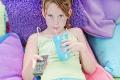 Muchacha que ve la TV en cama Foto de archivo libre de regalías