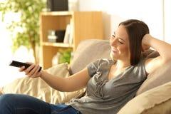 Muchacha que ve la TV en un sofá en casa Imagen de archivo