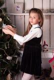 Muchacha que viste para arriba el árbol de navidad Fotos de archivo