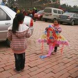 Muchacha que vuela una cometa en una ciudad, Chengdu, China Imagenes de archivo
