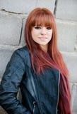 Muchacha rebelde del adolescente con el pelo rojo que se inclina en una pared Fotos de archivo