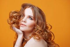 Muchacha redheaded hermosa con el pelo rizado lujoso Retrato del estudio en fondo amarillo Pelo excelente Fotos de archivo