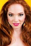 Muchacha redheaded hermosa con los pendientes coloridos Fotos de archivo