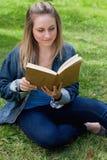 Muchacha relajada joven que lee un libro mientras que se sienta en la hierba Fotografía de archivo libre de regalías