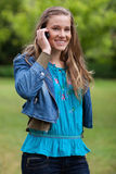 Muchacha relajada joven sonriente que habla en el teléfono Foto de archivo libre de regalías