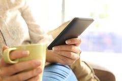 Muchacha relajada que comprueba el teléfono móvil en casa Foto de archivo