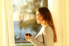 Muchacha relajada que considera a través de una ventana la puesta del sol Imágenes de archivo libres de regalías