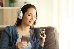 Muchacha relajada que escucha la música con los ojos cerrados Imágenes de archivo libres de regalías