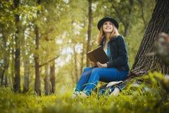 Muchacha relajada que lee un libro debajo de un árbol Imagenes de archivo