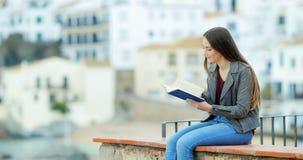Muchacha relajada que lee un libro en una repisa almacen de video