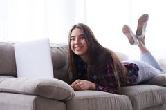 Muchacha relajada que miente en el sofá con el ordenador portátil Imagen de archivo libre de regalías