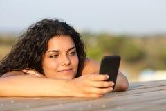 Muchacha relajada que mira medios sociales en teléfono elegante Foto de archivo libre de regalías