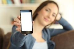 Muchacha relajada que muestra la pantalla elegante del teléfono en casa Foto de archivo