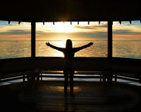 Muchacha relajante en la puesta del sol en el lago Imagenes de archivo