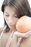 Muchacha Relaxed con la fruta anaranjada Imágenes de archivo libres de regalías
