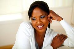 Muchacha relaxed encantadora que sonríe y que mira abajo Imagen de archivo