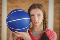 Muchacha resuelta que lleva a cabo un baloncesto Imágenes de archivo libres de regalías