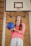 Muchacha resuelta que lleva a cabo un baloncesto Fotografía de archivo