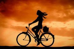 Muchacha retra de la puesta del sol en una bici Imagenes de archivo