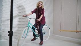 Muchacha retra en una bicicleta en estudio almacen de metraje de vídeo
